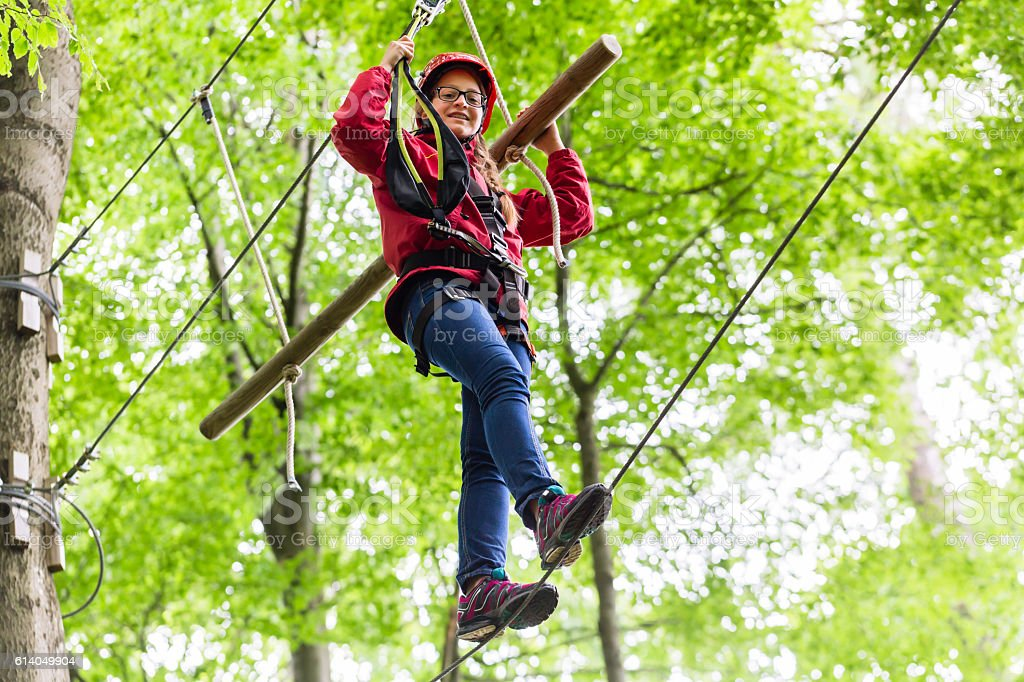 Child reaching platform climbing in high rope course stock photo