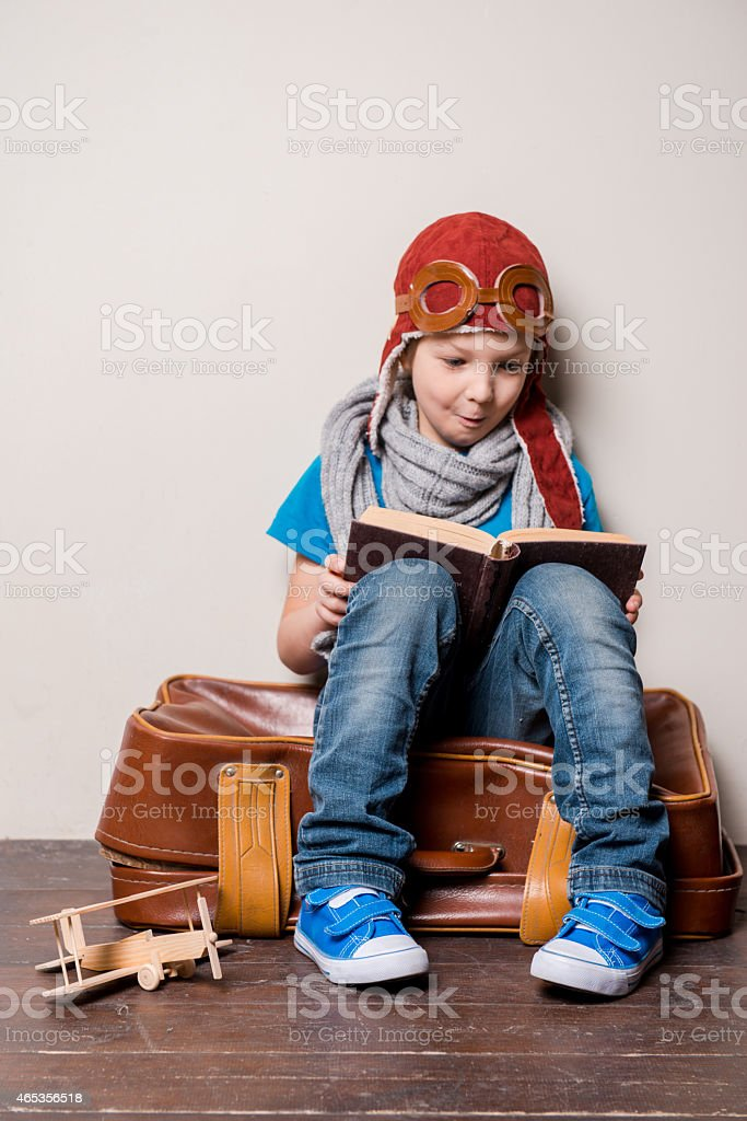Child reading a book in a traveling outfit stock photo