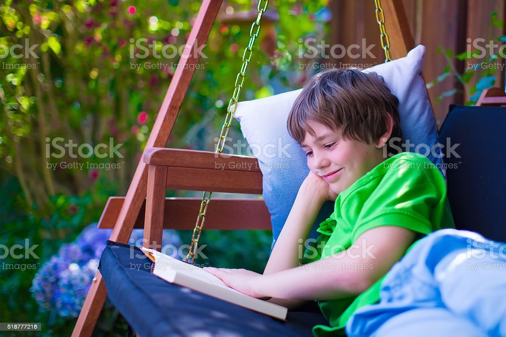 Child reading a book in the garden stock photo