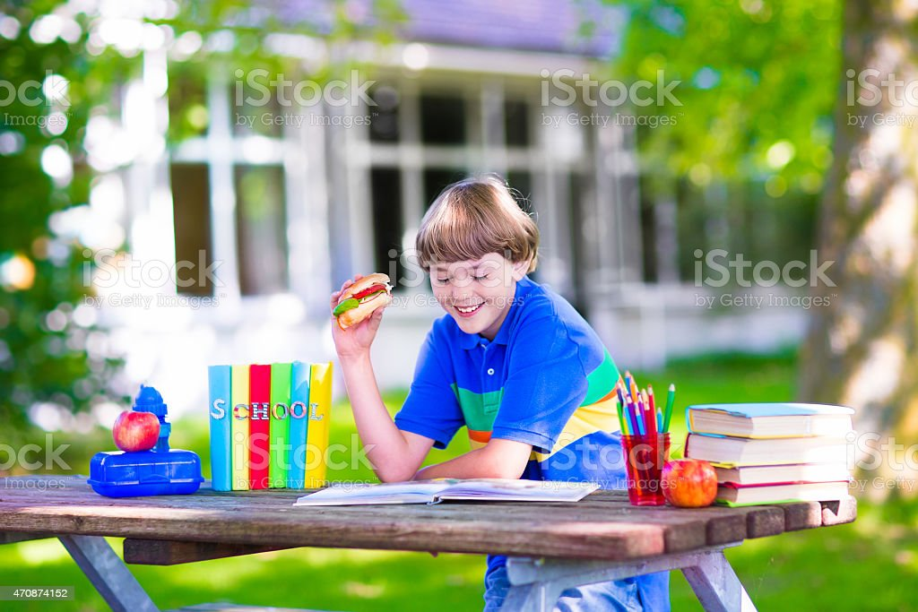 Child reading and eating sandwich at school yard stock photo