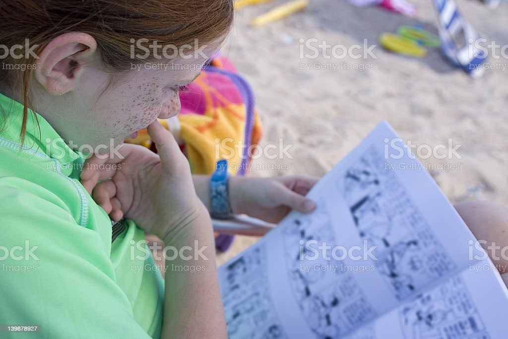 Child Reading on the Beach stock photo