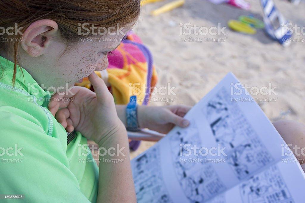 Child Reading on the Beach stock photo