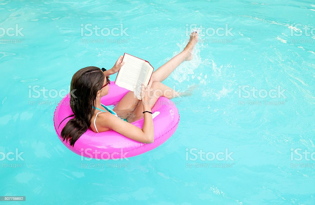 Child reading while floating on a pink lifesaver stock photo