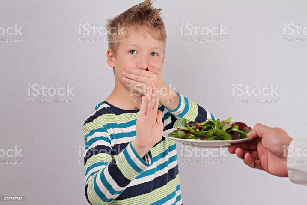 Child refuses to eat salad vegetables stock photo
