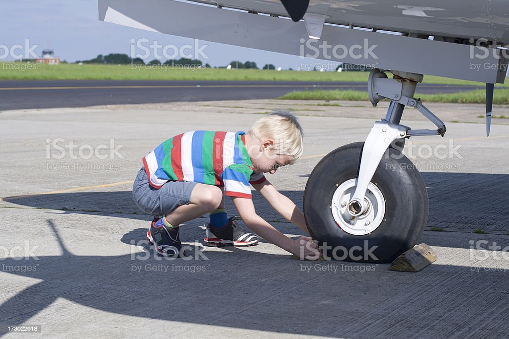 Child removing the chocks from under a plane stock photo