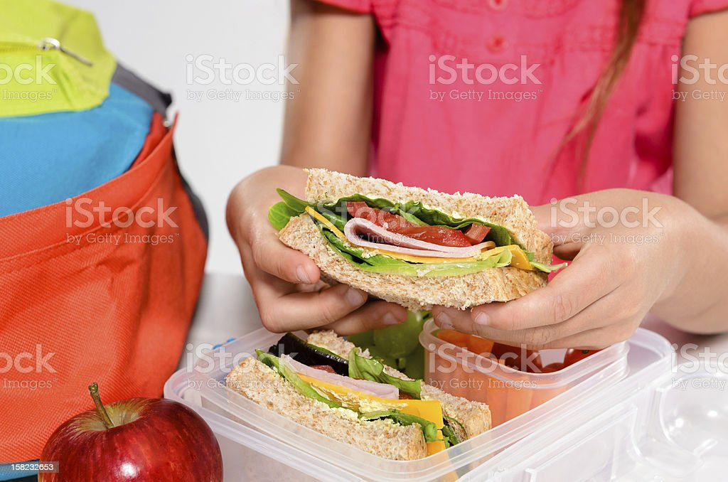 Child removing wholemeal sandwich out of lunchbox stock photo