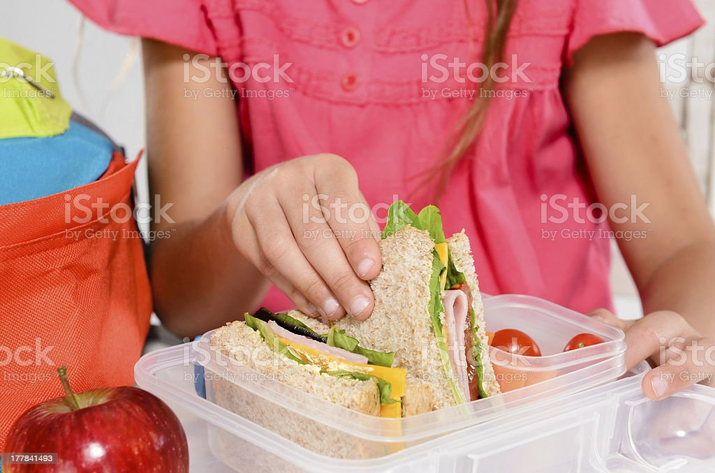 Child removing wholemeal sandwich out of lunchbox royalty-free stock photo
