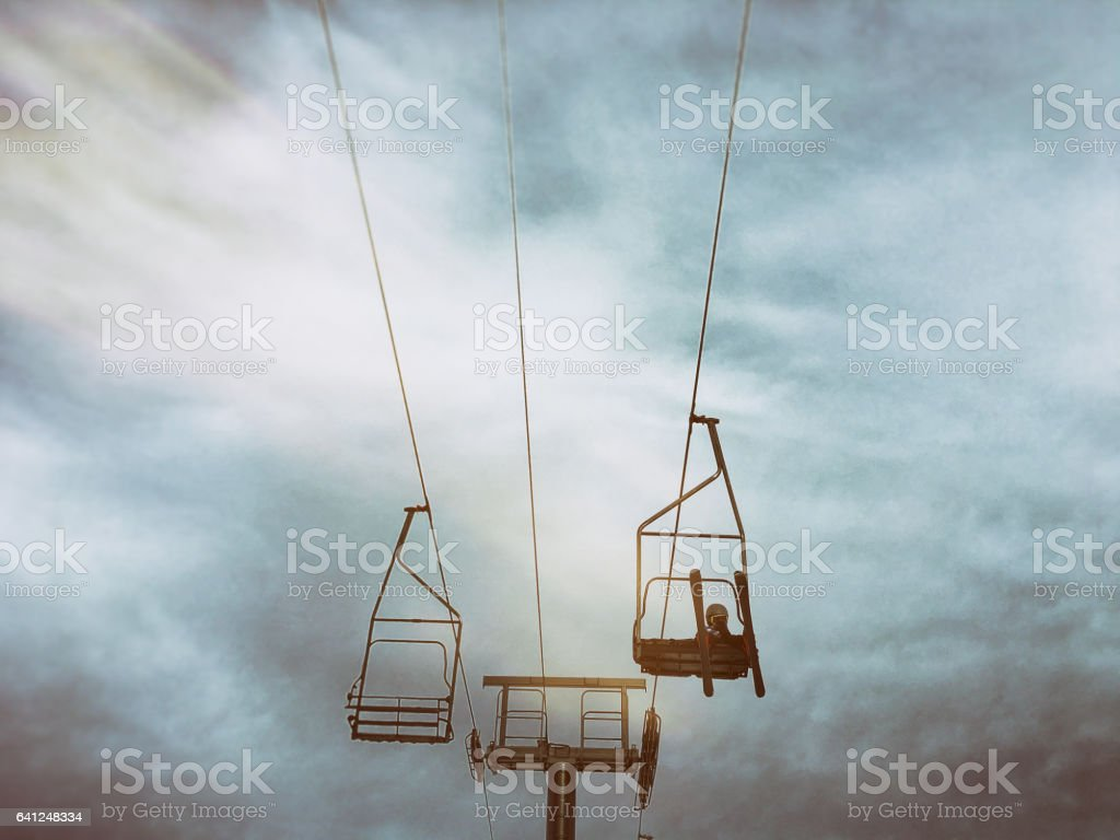 Child rides a chair lift by himself stock photo