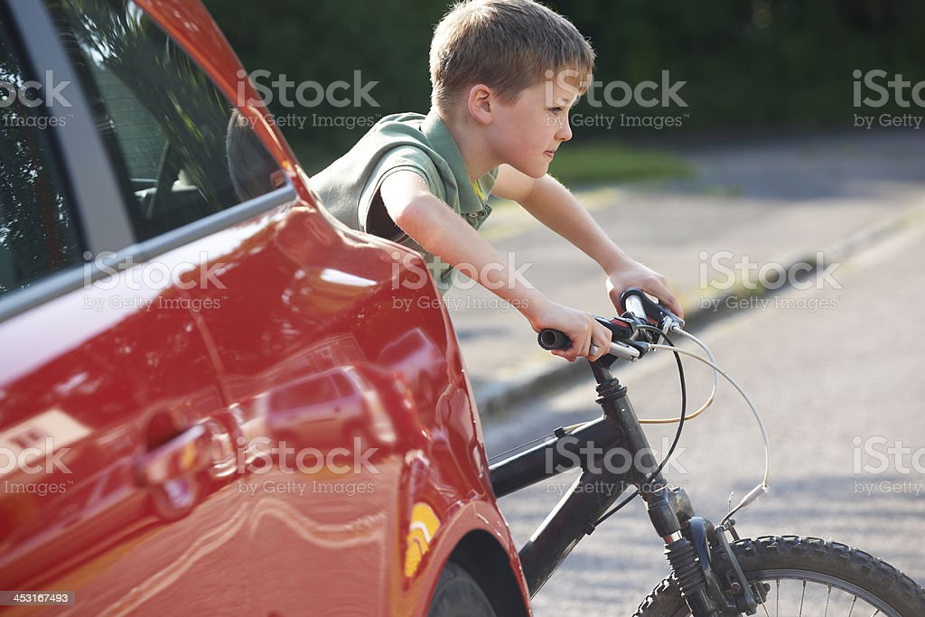 Child Riding Bike From Behind Parked Car royalty-free stock photo