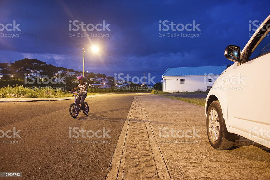 child riding bike in suburban area at sunset royalty-free stock photo