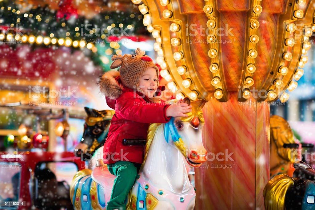 Child riding carousel on Christmas market stock photo