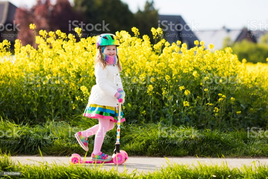 Child riding schooter on way to school stock photo