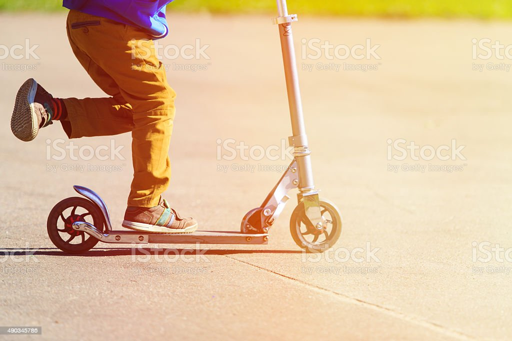 child riding scooter, active sport kids stock photo