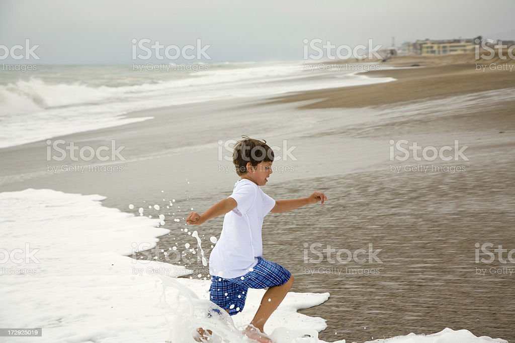 Child Running From Waves stock photo