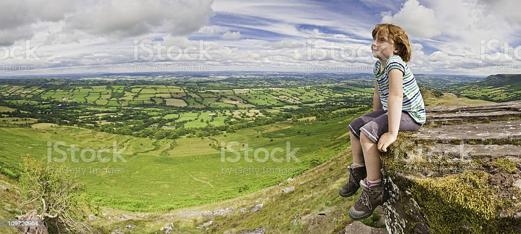 Child sat on mountain top overlooking green summer landscape panorama royalty-free stock photo