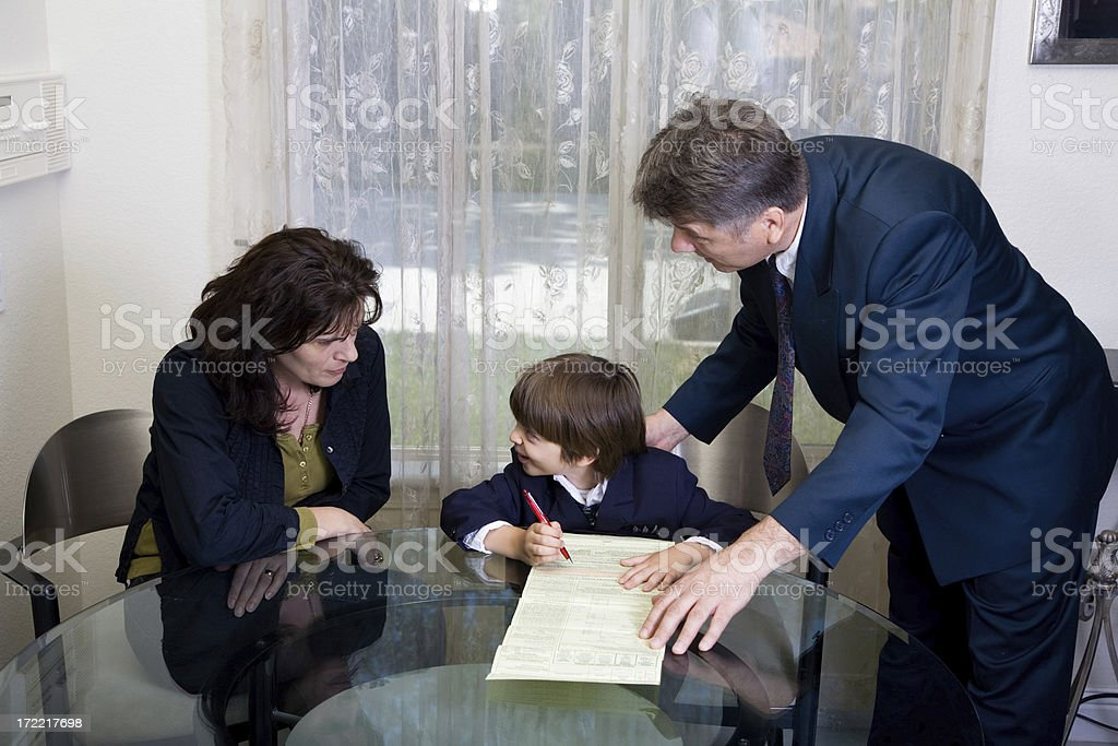 Child Signing Documents While Surrounded By Two Adults royalty-free stock photo