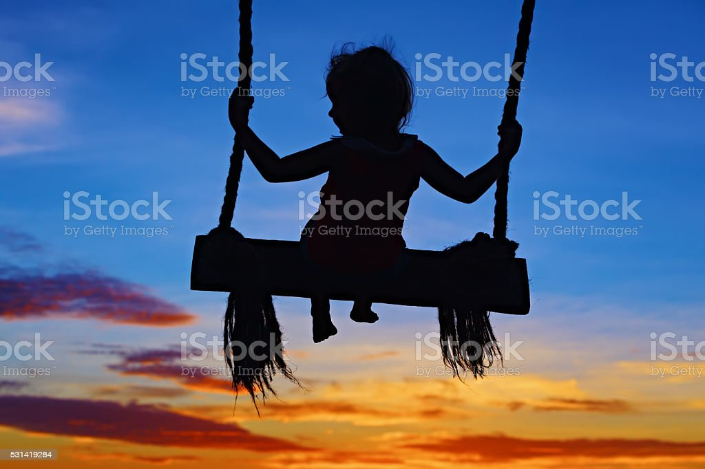 Child sit on swing on colorful sunset sky background stock photo