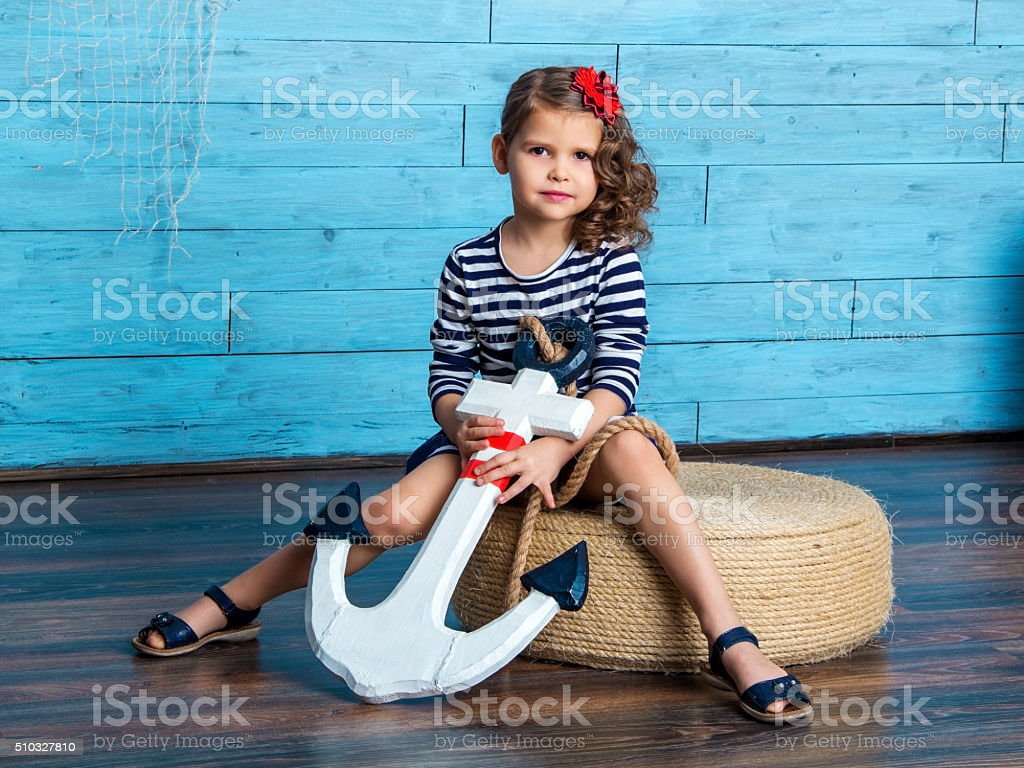 child sitting and holding an anchor stock photo