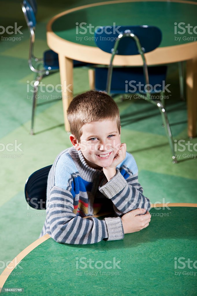 Child sitting at round table in school classroom stock photo