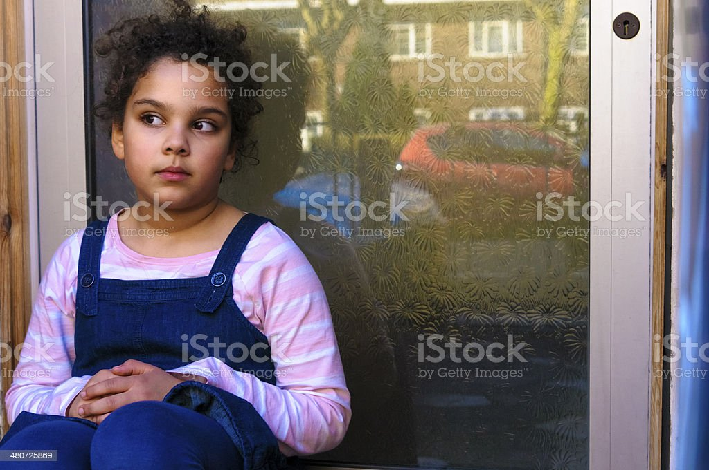 PEOPLE: Child (7-8) Sitting by the Door royalty-free stock photo