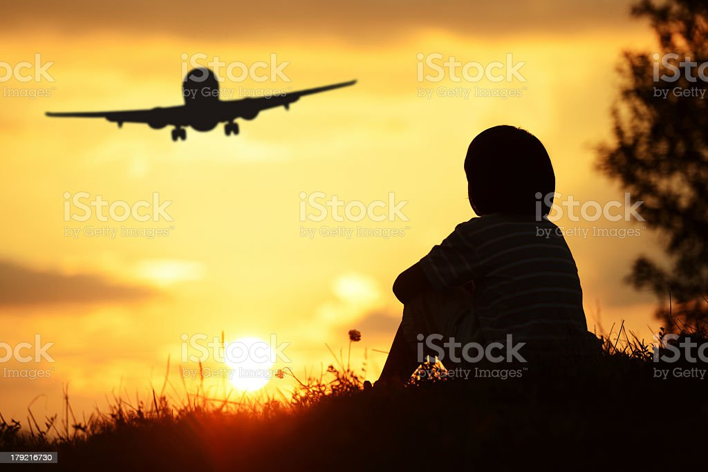 Child sitting during summer sunset looking at airplane stock photo