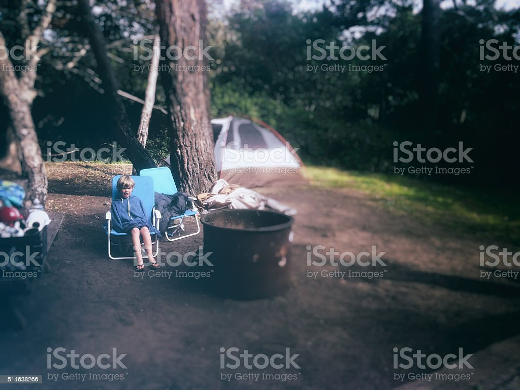 Child sitting in a campground with tent in background stock photo