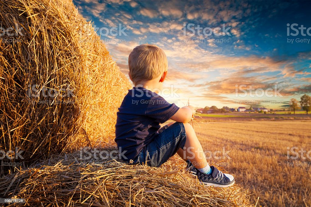 Child sitting on bales of straw stock photo