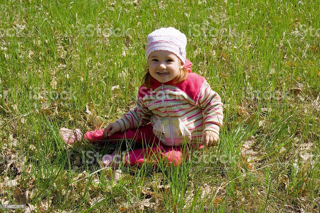 Kind sitzt auf Gras Lizenzfreies stock-foto