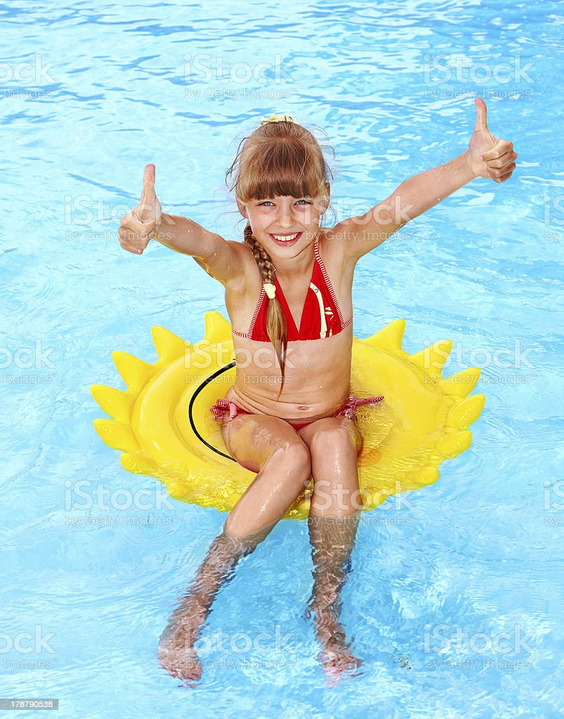 Child sitting on inflatable ring thumb up. royalty-free stock photo
