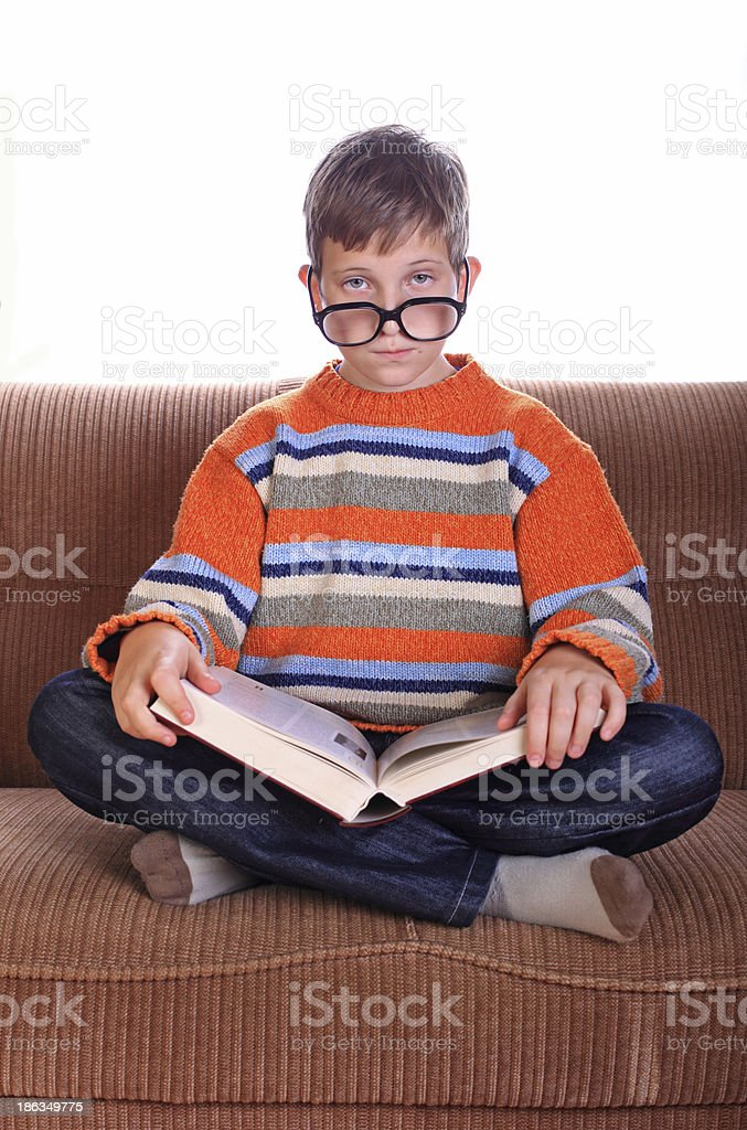 Child sitting on sofa with book royalty-free stock photo