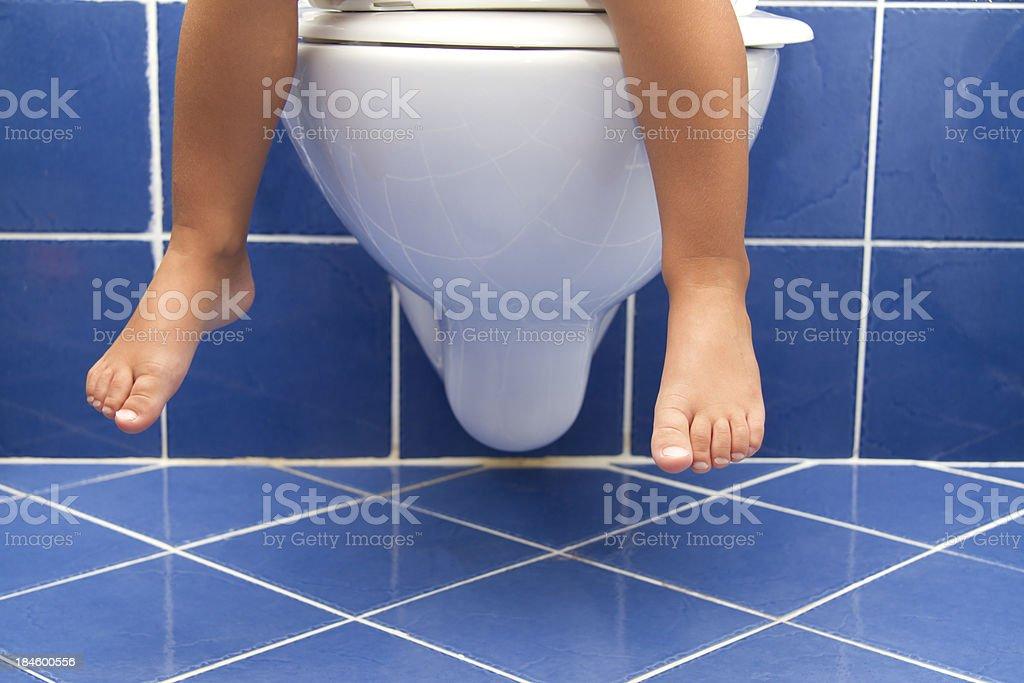 Child sitting on the toilet stock photo
