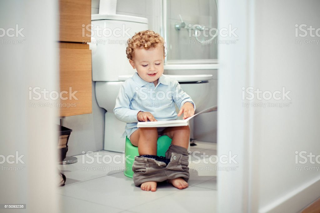 Child sitting on the toilet stock photo