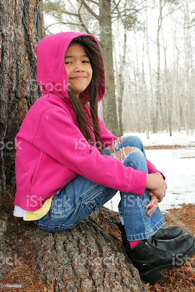 Child sitting under tree in winter royalty-free stock photo
