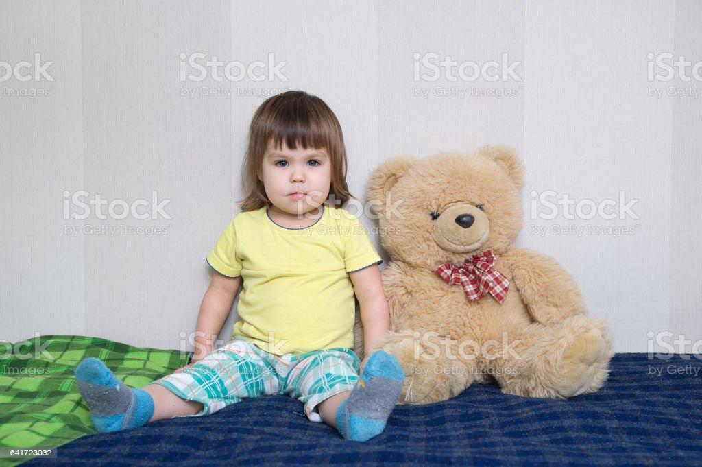 child sitting with teddy bear big toy indoor, childhood friendship...