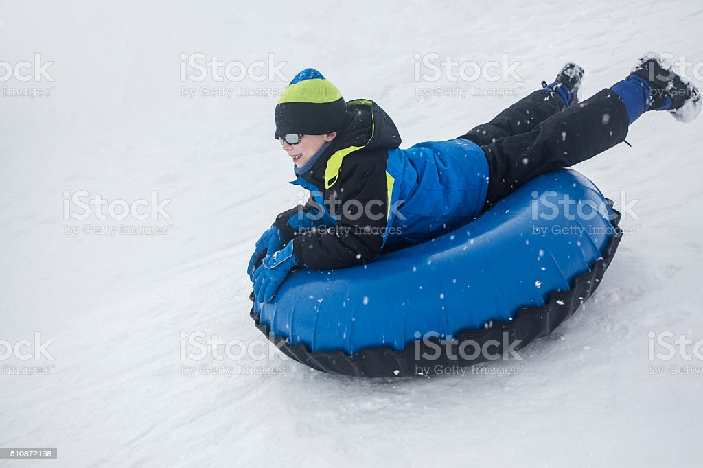 Child sledding down a hill on a snow tube stock photo