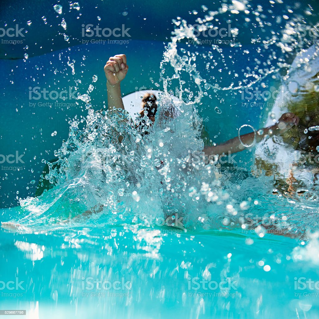 Child sliding and splashing in water park stock photo
