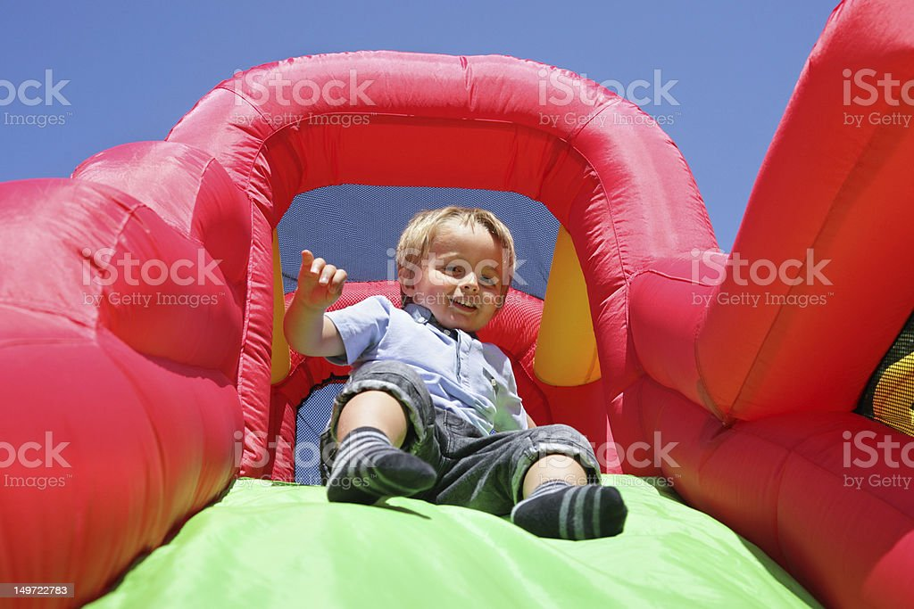 Child sliding down an inflatable bounce castle slide stock photo