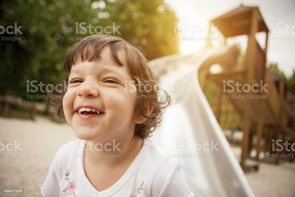 Child smiling after slide at park stock photo