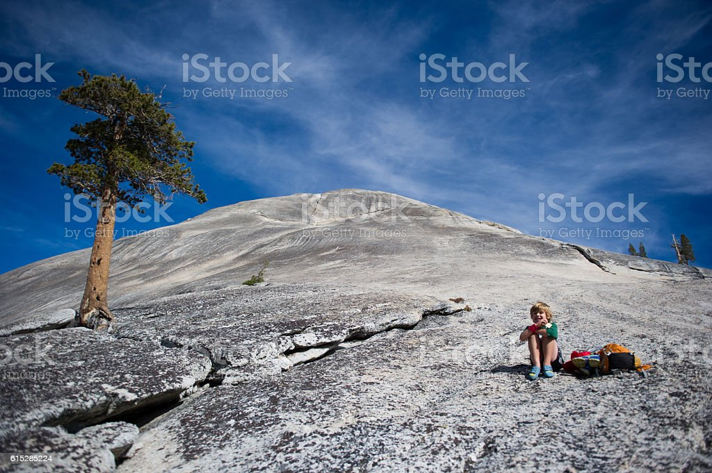 Child snacking on dome in Yosemite Valley, Ca stock photo
