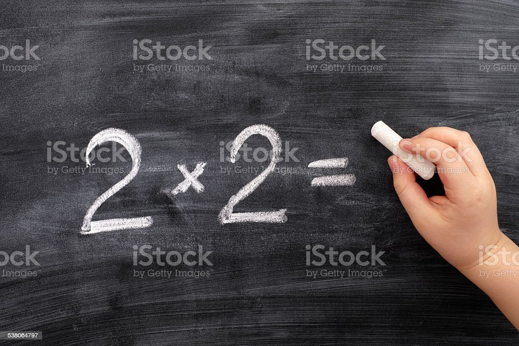 Child solving math problem on the blackboard stock photo