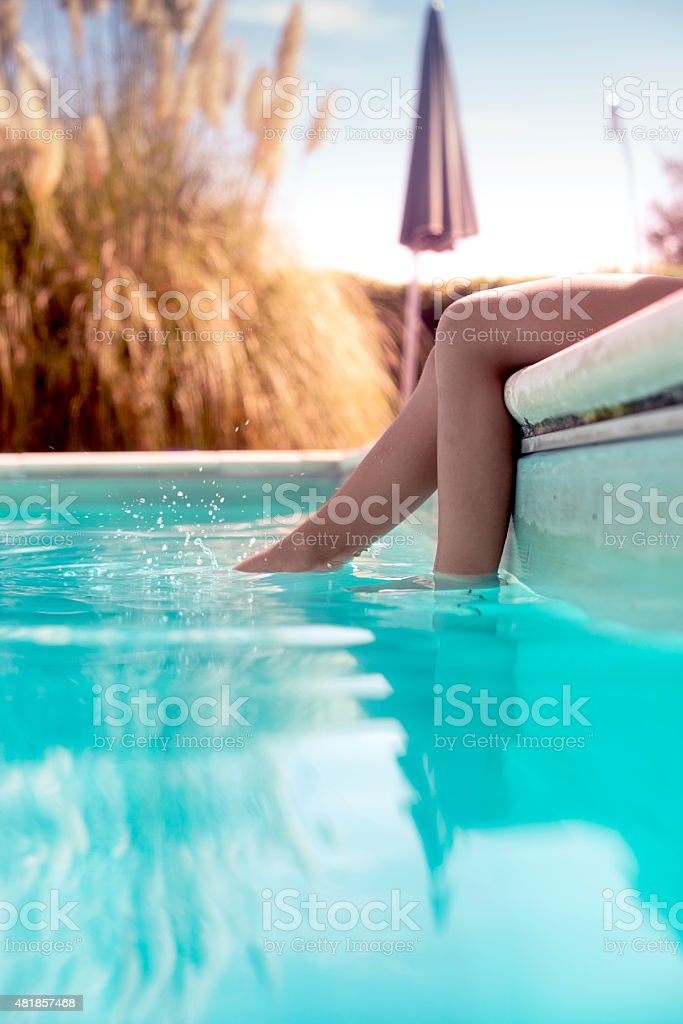 Child splashing feet in the pool stock photo