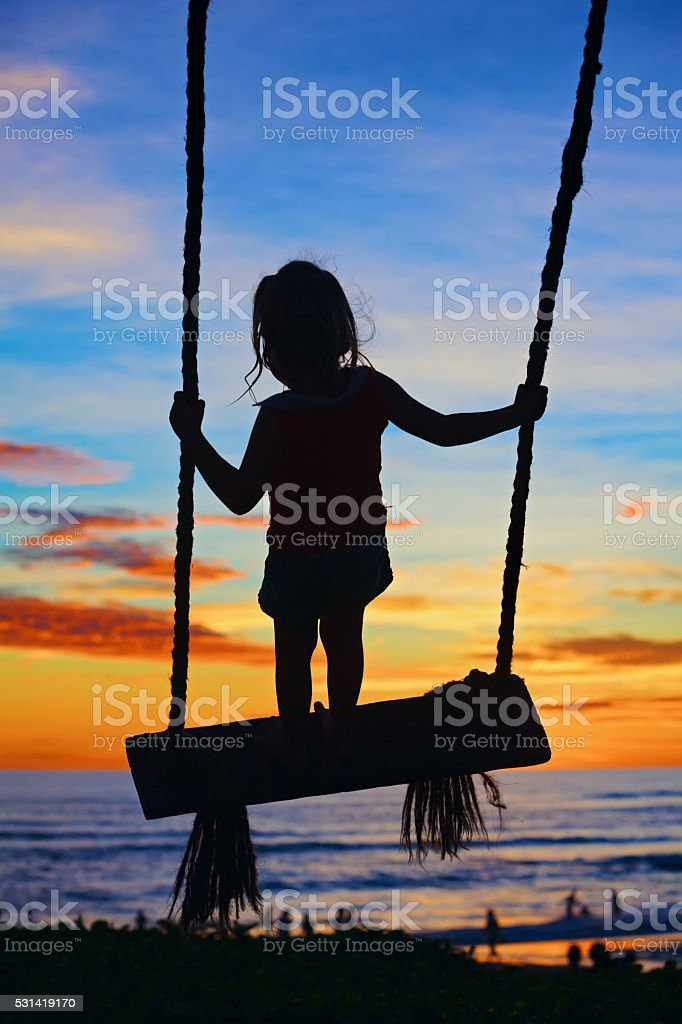 Child stand on swing on colorful sunset sky background stock photo