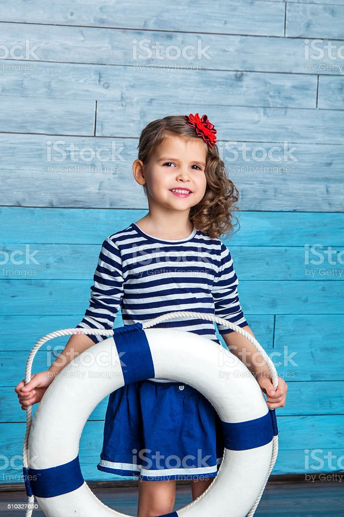 child standing and holding a lifebuoy stock photo