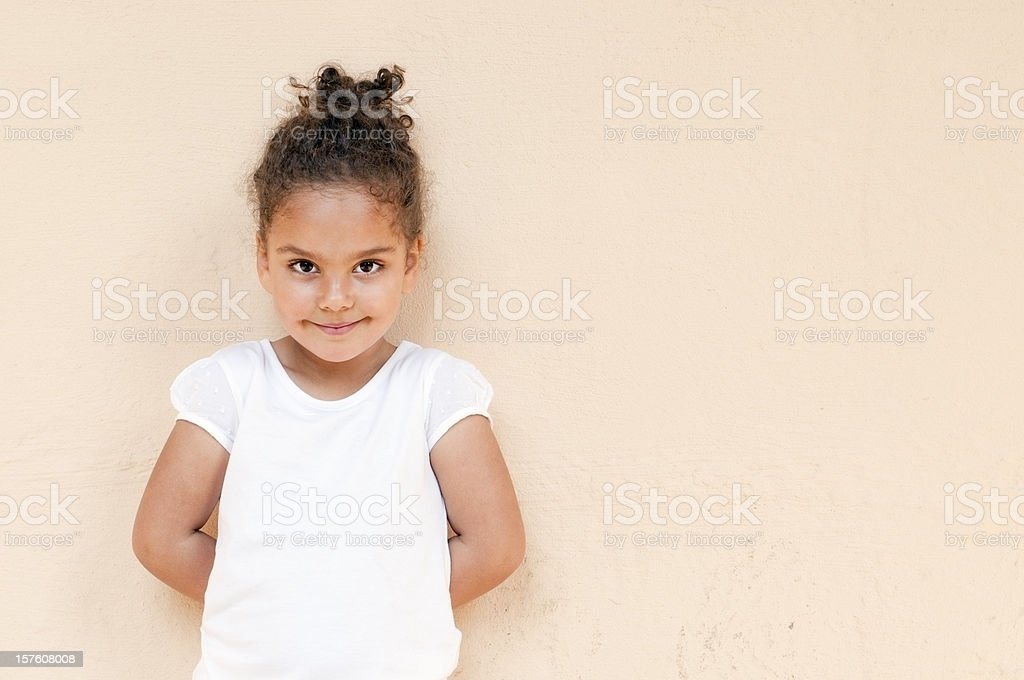 Child Standing Up Against Wall with Hands Behind Her Back royalty-free stock photo