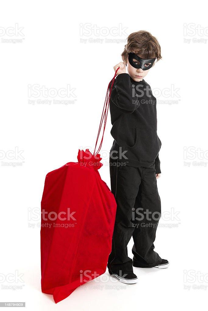 Child stealing Santa's sack royalty-free stock photo
