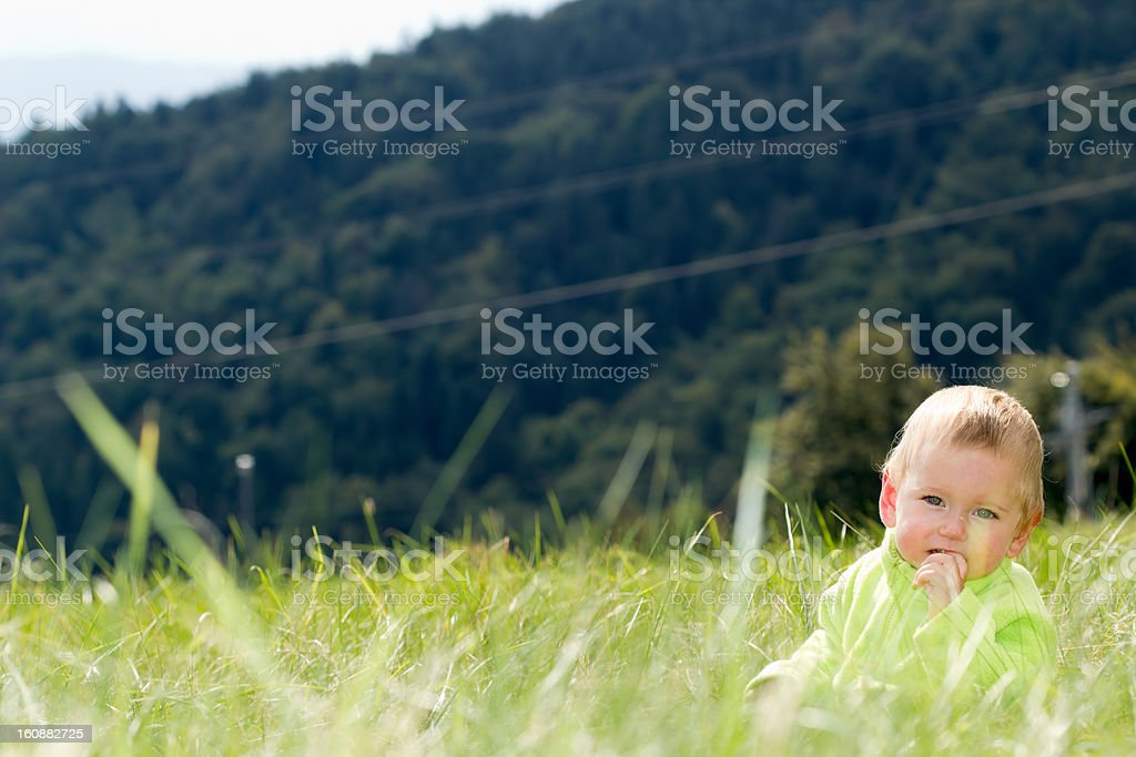 Child sucking finger and sitting in the grass royalty-free stock photo