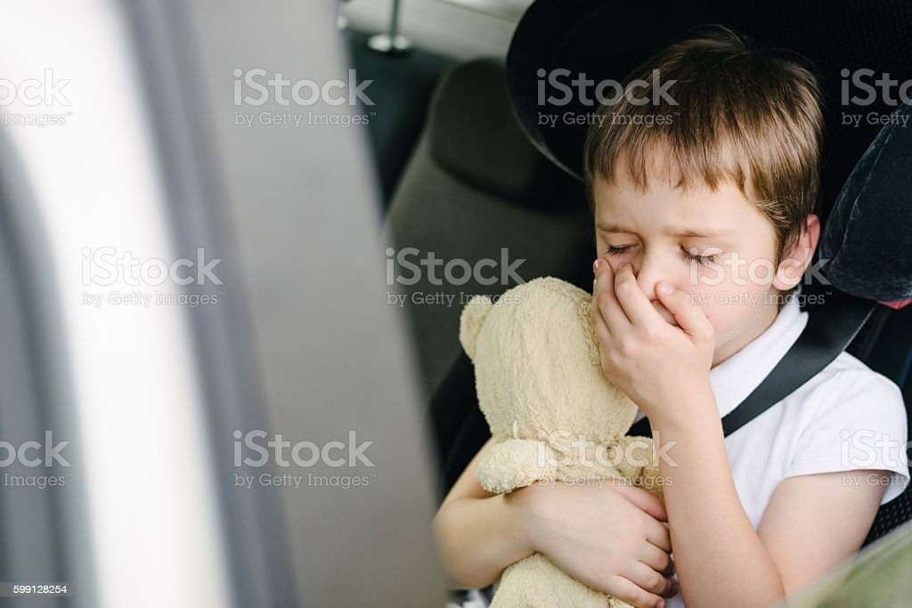 Child suffers from motion sickness in car stock photo
