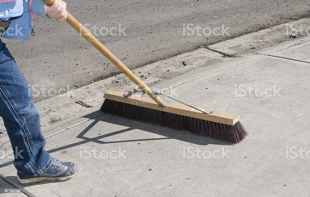 Child Sweeping / Cleaning Sidewalk With Wide Broom stock photo