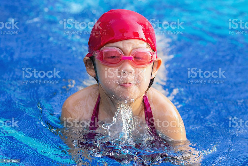 Child Swimming Breaststroke in Swimming Pool stock photo