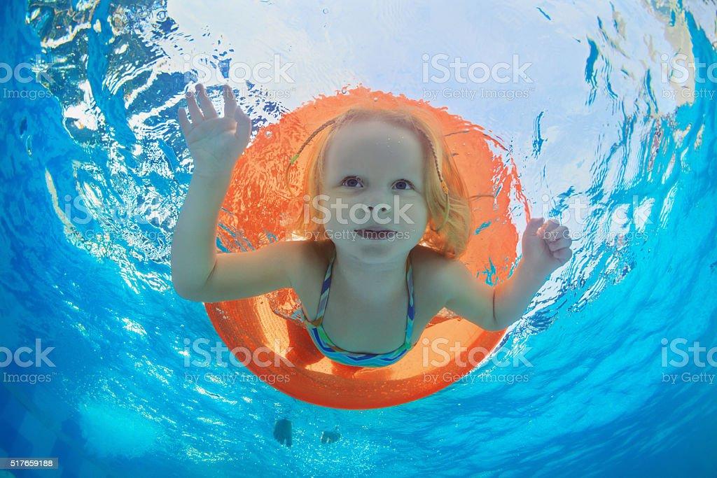 Child swimming on orange inflatable tube in pool stock photo
